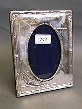 A silver photo frame with relief trailing
