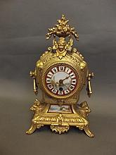A gilt and brass mantle clock with ceramic panels