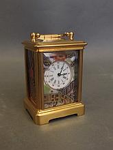 A miniature porcelain and brass carriage clock