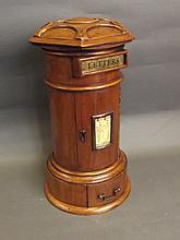 A carved walnut table top post box with a