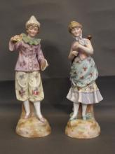 A pair of early C20th Continental ceramic figures of a girl holding a guitar and a boy dressed as a clown holding cymbals, impressed mark to base, 12½