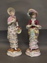 A matched pair of C19th porcelain figures of young ladies in crinolines and bonnets, impressed mark to base, 10½