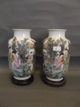 A pair of Chinese Republic period pottery vases painted in coloured enamels with figures in a garden setting, on hardwood stands, 12½