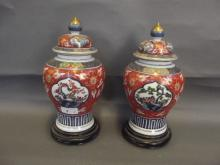 A pair of early C20th Japanese Imari vases and covers on hardwood stands, 6 character mark, 11½