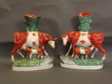 A pair of Staffordshire spill vases in the form of a cow and calf standing by a stream, circa 1870, on oval gilt lined bases, 12