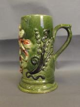 An English pottery tankard with raised decoration of a lion wearing a crown and holding a sword, flanked by woodland flowers beneath a heavy green glaze, circa 1870, 7½