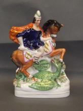 A C19th Staffordshire equestrian figure group of George the dragon slayer, on an oval gilt lined base, circa 1865, 8½