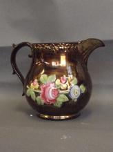 A late C19th copper lustre jug with raised flower decoration and painted floral patterns, 6