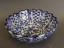 An Oriental blue and white pottery bowl with fluted rim and decorated with