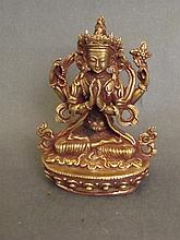 A Tibetan copper and gilt figure of a seated goddess, 3½'' high