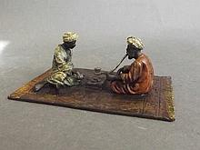 A cold painted bronze figure group of two Arab gentlemen smoking and playin