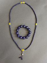A lapis lazuli bead necklace with white metal Buddha's head pendant, and a