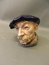 A glazed terracotta portrait of a gentleman in a beret, indistinctly signed