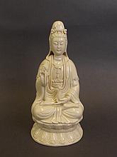 A Chinese blanc-de-chine porcelain figure of Quan Yin holding a vase, impre