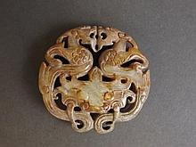 A chinese calcified jade pendant with carved and pierced twin dragon decora