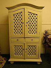 A painted cabinet with arched top, latticed doors and two drawers, standing