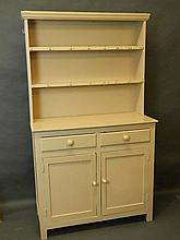 A small painted dresser with shelved upper section on a base of two drawers
