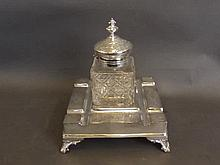 A large silver plate and cut glass inkwell on quadruped feet, 7'' square