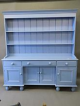 A painted pine dresser of three drawers over four cupboards with delft rack
