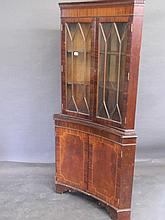 A Regency style mahogany standing corner cupboard of concave form with astr