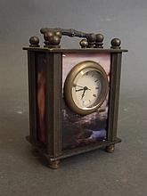 A miniature brass cased carriage clock decorated with cold enamel panels de
