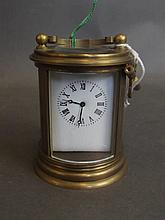 A miniature cylindrical brass cased carriage clock, key present, 2¾'' high