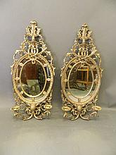 A pair of silvered composition two branch wall sconces with oval mirrors, 1
