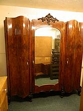 An Italian figured walnut shaped front wardrobe with central mirrored door,