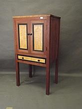 A small contemporary hardwood press cupboard with satinwood door panels and