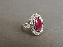 A 14ct white gold and diamond ring set with an oval cut ruby, approximately