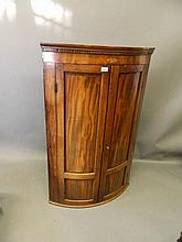 A George III mahogany and inlaid bow fronted two door hanging corner cupboa