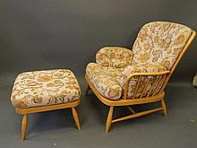 An Ercol beech wood armchair and matching stool, en suite to previous lot,