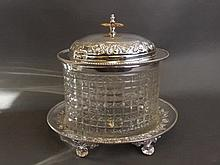A silver plate and cut glass biscuit barrel on a silver plate stand, with f