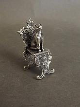 A small silver figure of a cat seated on an ornate chair, 2'' high