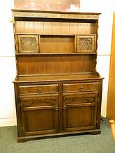 An Ercol dark oak dresser with carved frieze and two glazed doors, 49'' x 1