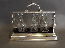 A silver plated three-bottle tantalus with key, 9½'' wide