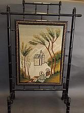A faux bamboo fire screen with a tapestry panel depicting two people lookin