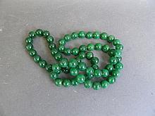 A long string of green jade beads, 32'' long