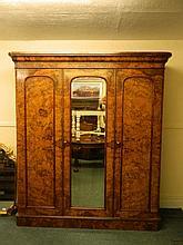 A good Victorian burr walnut triple door wardrobe with central mirrored doo