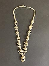 A graduated bone necklace with carved feature beads in the form of elephant