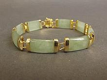 A Chinese apple jade bead bracelet with gilt metal mounts, 7½'' long