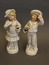A pair of C19th Continental porcelain figures of a boy and girl carrying baskets, 8½'' high (AF)