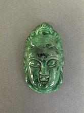 A Chinese mottled spinach jade pendant carved in the form of a goddess' head, 1½'' long