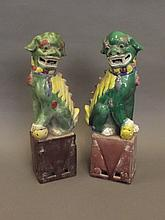 A pair of Chinese pottery figures of Fo dogs with green, yellow, brown and blue glaze decoration, 12¼'' high (AF crack to leg)