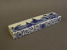 A Chinese blue and white porcelain wrist rest decorated with figures in garden scenes, 8'' x 2''