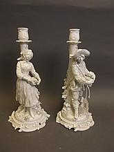 A pair of C19th German white glazed figural candlesticks, crossed swords mark, 11¾'' high
