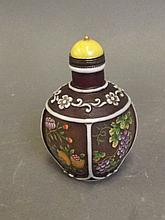 A brown composite snuff bottle with raised floral and painted enamel fruiting tree decoration, 4 character mark to base, 2½'' high