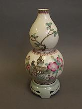 A Chinese double gourd shaped porcelain vase with painted enamel decoration of birds amongst trees and inscription verso, standing on an integral pierced porcelain stand, seal mark to base, 9¾'' high