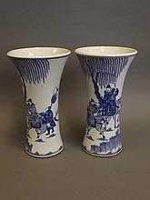 A pair of Chinese blue and white porcelain vases decorated with travellers on horseback, with flared rims, 9½'' high