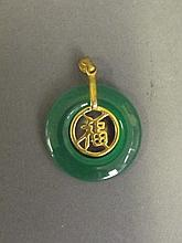 A Chinese apple jade and gilt metal circular pendant with character inscription, 1'' diameter